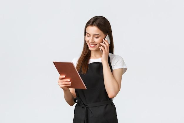 Supermarkt werknemers, kleine bedrijven en coffeeshops concept. de leuke glimlachende verkoopster in zwarte schort bevestigt orde, sprekend aan klant op telefoon en bekijkend digitale tablet