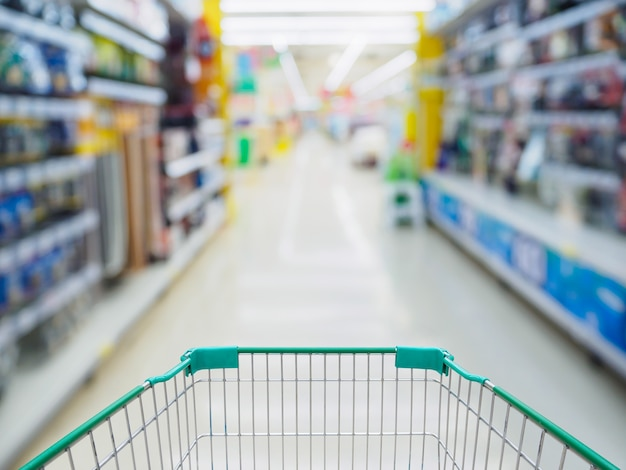 Supermarktdoorgang met lege groene winkelwagen