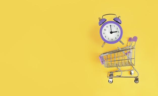 Supermarktkarretje en violette wekker op een gele achtergrond met exemplaarruimte. koop tijd, druk concept.