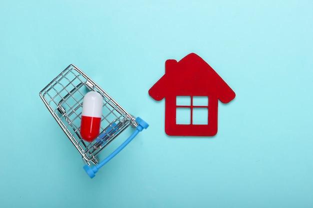 Supermarktkarretje met pillencapsule, beeldje van het ziekenhuisgebouw op blauwe achtergrond. bovenaanzicht