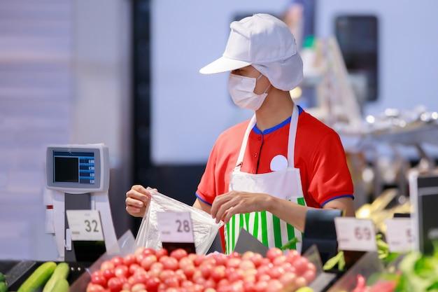 Supermarktpersoneel in medisch beschermend masker die bij supermarkt werken