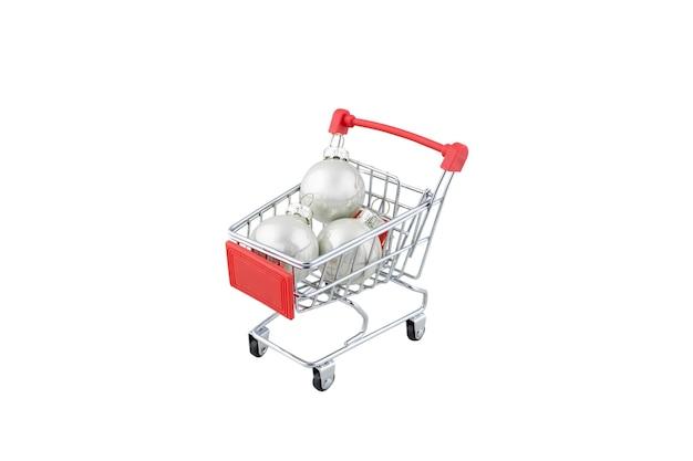 Supermarktwagen met drie witte kerstballen.