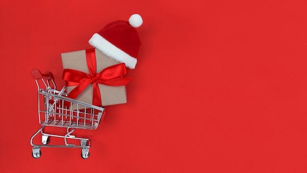 Supermarktwagen met een geschenkdoos en kerstmuts
