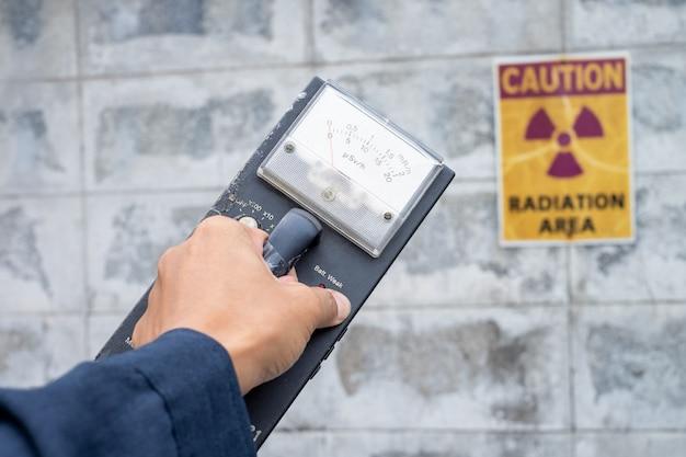 Supervisor gebruikt de meetmeter om het stralingsniveau in de radioactieve zone te controleren