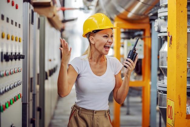 Supervisor in werkpak met beschermende helm op hoofd schreeuwen over walke talkie op haar werknemer.