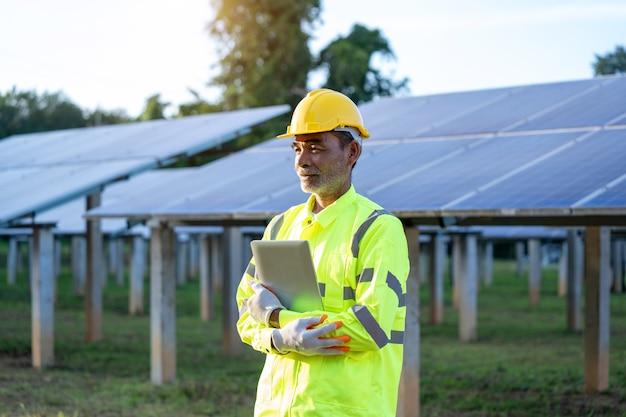 Supervisor ingenieurs mannen met veiligheidsvest en veiligheidshelm staan voor zonnepanelen.