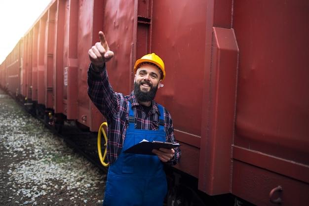 Supervisor van de spoorwegarbeider die lading controleert en naar een van de goederentreinwagons wijst