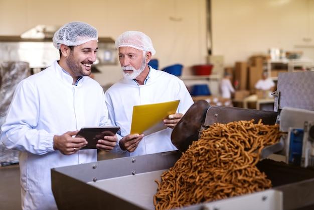 Supervisors in uniformen die de kwaliteit van voedsel in de voedselfabriek controleren. jongere tablet terwijl oudere map met documenten vasthoudt.