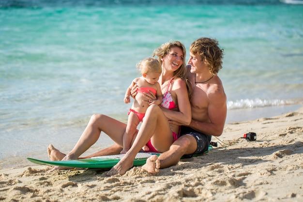Surfen. gelukkige familie zit op de surfplank. concept over familie, sport en plezier