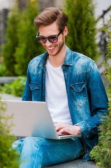 Surfen op het web buitenshuis. glimlachende jonge man die op laptop werkt terwijl hij buiten zit