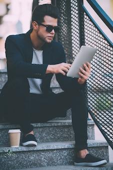 Surfen op het web buitenshuis. knappe jongeman in slimme vrijetijdskleding die aan digitale tablet werkt terwijl hij buiten op de trap zit