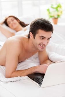 Surfen op het web in bed. vrolijke jonge man die laptop gebruikt terwijl hij in bed ligt met zijn vriendin