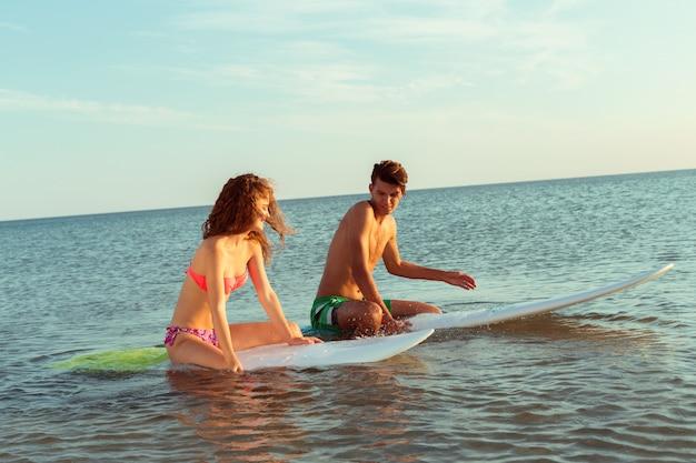 Surfend paar dat op surfplanken in overzees leunt