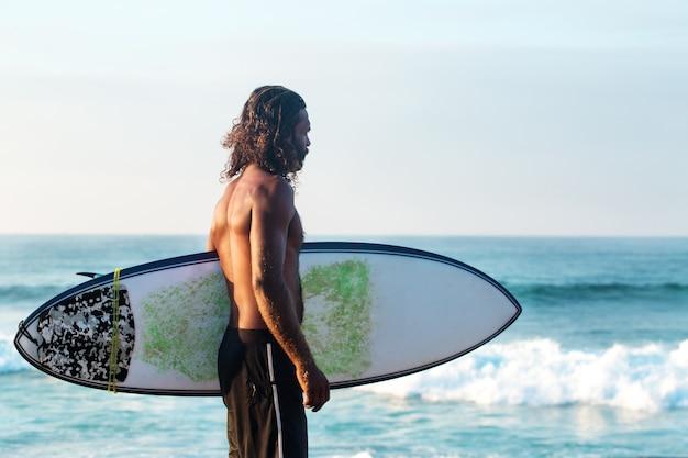 Surfer die een surfplank bij de oceaankust houdt