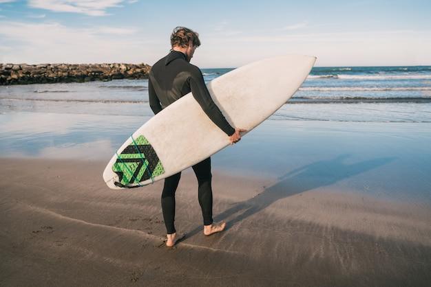 Surfer die het water ingaat met zijn surfplank.
