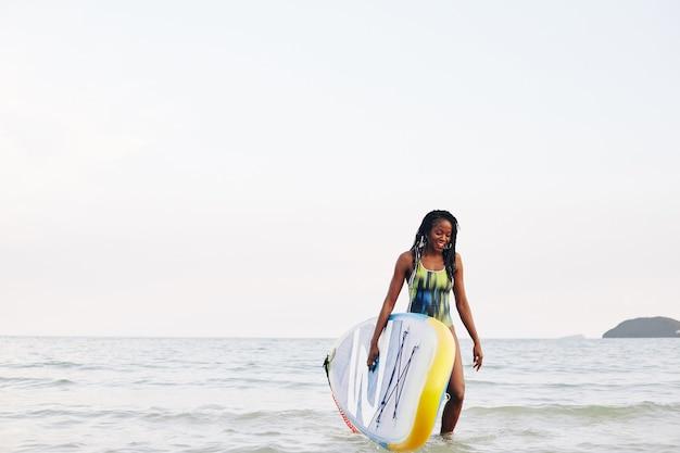 Surfer die uit zee loopt