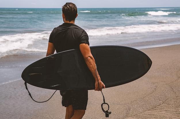 Surfer in een zwart wetsuit is klaar om het water in te gaan.