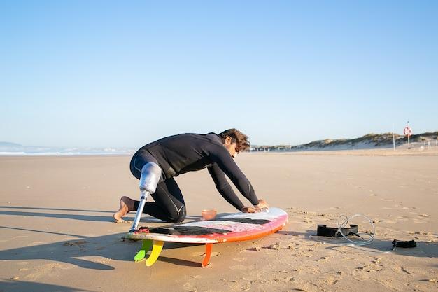 Surfer in wetsuit die kunstledemaat draagt, surfplank op zand op oceaanstrand in de was zetten