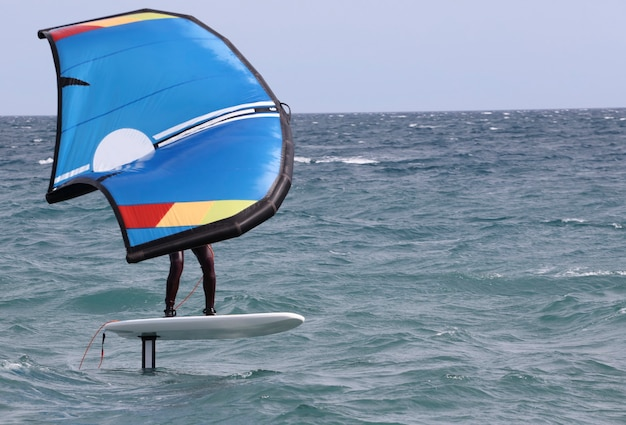 Surfer in windfoil zeilen door de golven