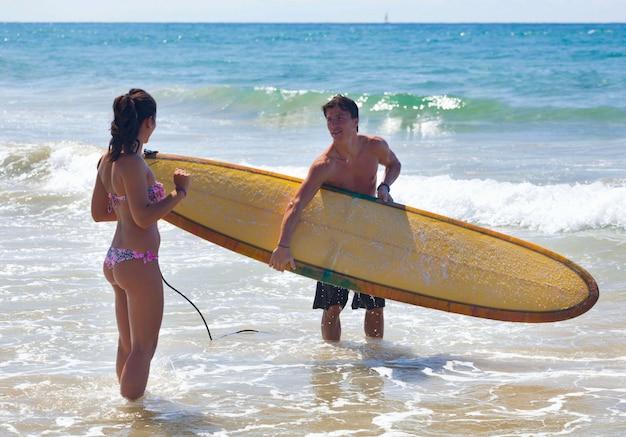 Surfer legt de theorie van surfen aan een jonge vrouw uit