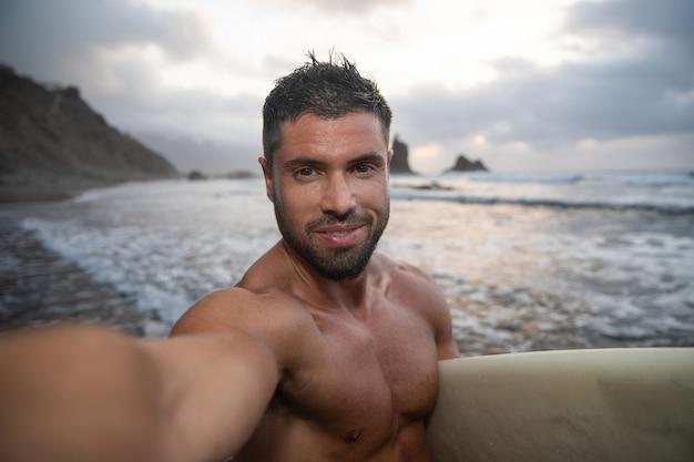 Surfer maakt een selfie op het strand tijdens zonsondergang, hij houdt zijn surfplank vast en lacht. jonge aantrekkelijke man op het strand - vrolijke persoon die extreme sport beoefent