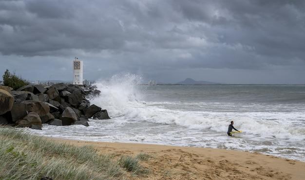 Surfer met een gele surfplank die geniet van de golven van de sunshine coast van australië