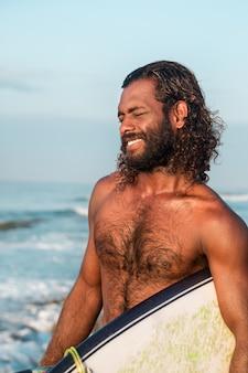 Surfer met een surfplank in de buurt van de oceaan