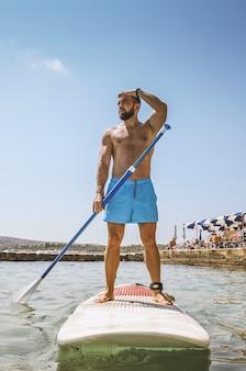 Surfer opstaan op paddle board op zee