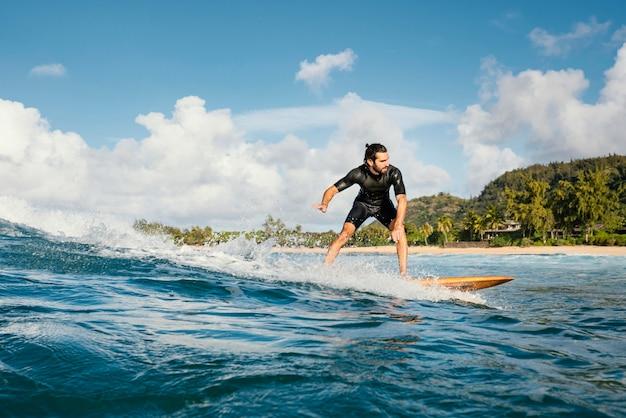 Surfer rijden golf bij daglicht