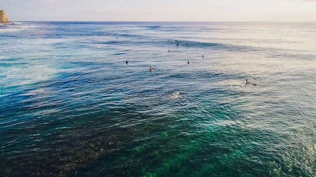 Surfer rijden op golven in de oceaan zonsondergang, bovenaanzicht