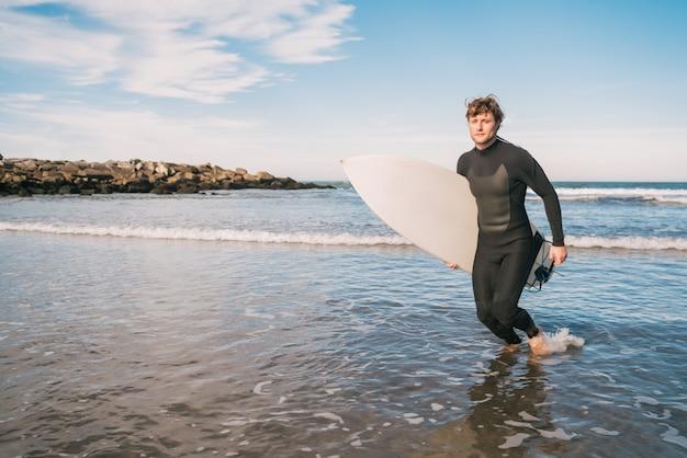 Surfer verlaat het water met surfplank onder zijn arm