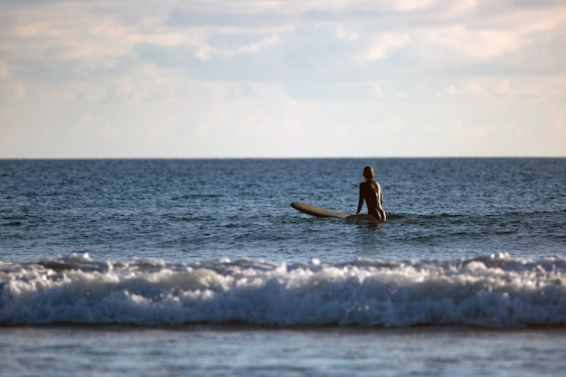 Surfer zittend in de oceaan bij zonsondergang