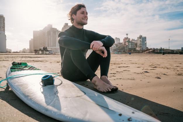 Surfer zittend op zandstrand en naast surfplank.