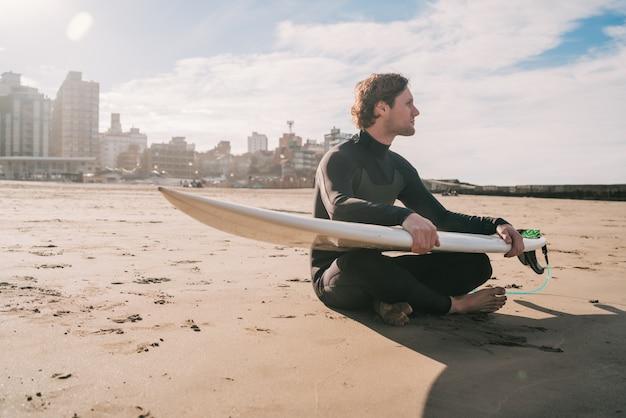 Surfer zittend op zandstrand met surfplank.