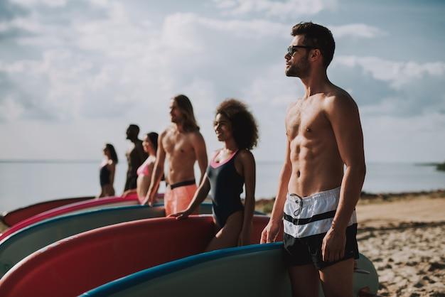 Surfers in zwemkleding permanent op het strand,