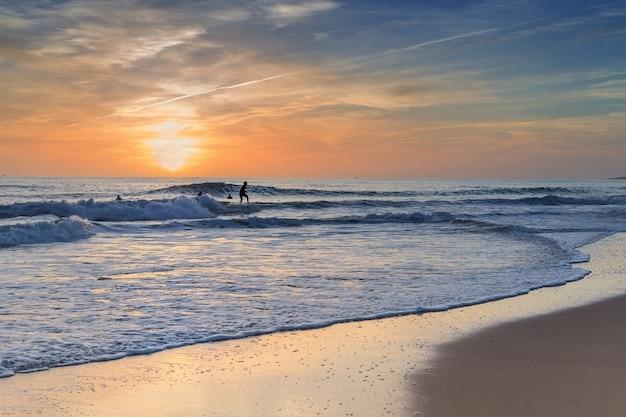 Surfers oefenen surfen bij zonsondergang.