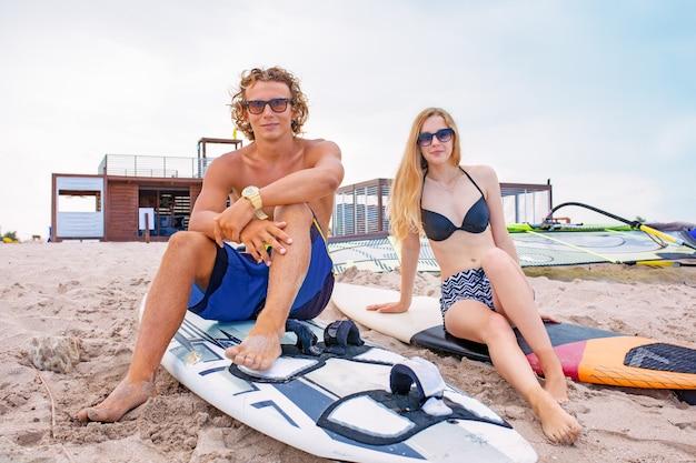 Surfers op het strand - glimlachend paar surfers die op het strand lopen en plezier hebben in de zomer