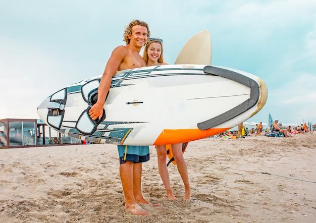 Surfers op het strand - glimlachend paar surfers die op het strand lopen en pret hebben in de zomer. extreme sport en vakantie concept