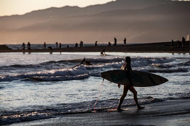 Surfersilhouet die door het overzees bij zonsondergang lopen
