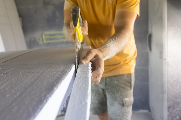 Surfplank die schrijnwerker maakt die veiligheidsademhalingstoestel draagt die surfplank leeg zagen gebruikend handzaag
