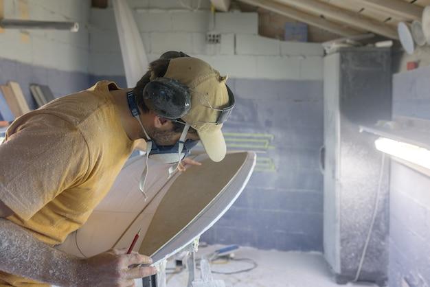 Surfplank die shaper maakt die een lege surfplank meet met een templatecraftsman op het werk