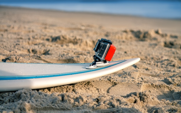 Surfplank met bijgevoegde actiecamera ligt op het zand op het strand
