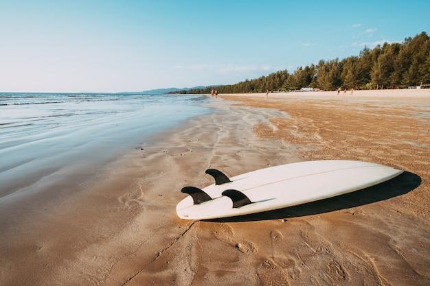 Surfplank op zand tropisch strand met zeegezicht kalme overzees en hemelachtergrond.