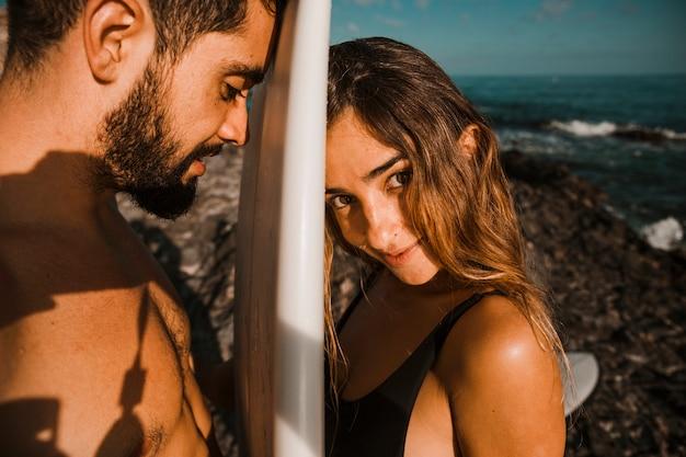 Surfplank tussen jonge vrouw en man op kust