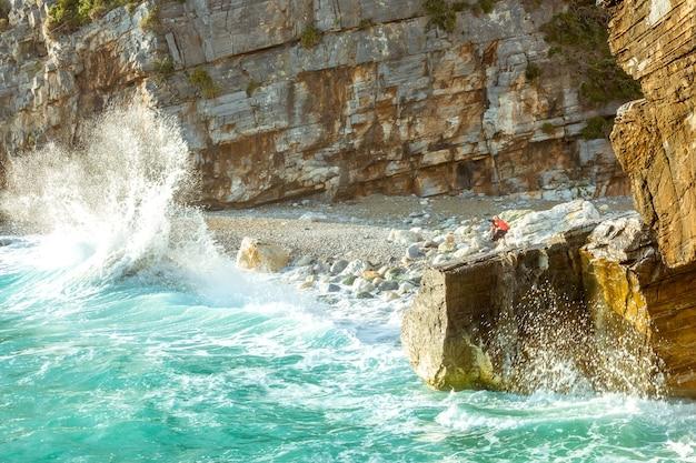 Surfspray op de rotsachtige kust en fotograaf op het strand