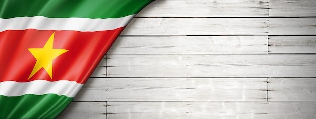 Surinaamse vlag op oude witte muur. horizontale panoramische banner.