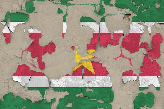 Suriname vlag afgebeeld in verfkleuren op oude verouderde slordige betonnen muur close-up.