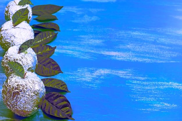 Surrealisme vijf appels in de schaal folie met natuurlijke groene bladeren.