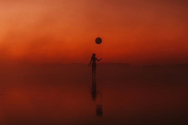 Surrealistisch silhouet van een meisje met een ballon in haar hand op het water bij zonsopgang in de mist in de zomer. concept van vrijheid en harmonie