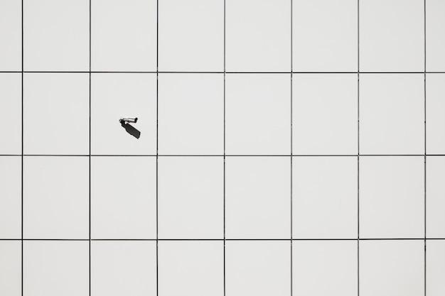 Surveilancecamera op de muur op geometrische patroonachtergrond